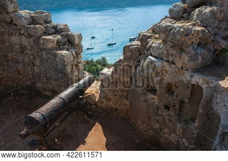 Old rusty cannon at ancient fortress wall of Simena (Kalekoy) castle overlooking tranquil Mediterranean sea, Popular tourist attraction in Turkey