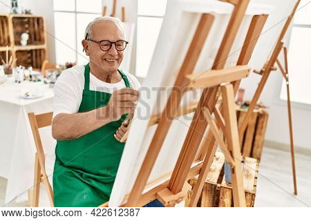 Senior grey-haired artist man smiling happy painting at art studio.