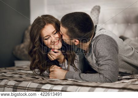 Beautiful Woman And Her Beloved Boyfriend Are Having Fun At Home, Lying On The Bed. A Man Kisses His