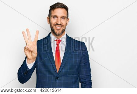 Handsome man with beard wearing business suit and tie showing and pointing up with fingers number three while smiling confident and happy.