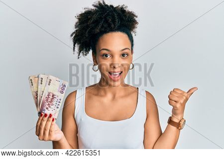 Young african american girl holding 500 new taiwan dollars banknotes pointing thumb up to the side smiling happy with open mouth