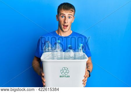 Young caucasian man holding recycling wastebasket with plastic bottles celebrating crazy and amazed for success with open eyes screaming excited.