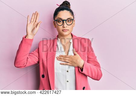 Beautiful middle eastern woman wearing business jacket and glasses swearing with hand on chest and open palm, making a loyalty promise oath