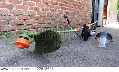 A Petrol-powered Hand Lawnmower Lying On The Asphalt In Front Of A Brick Building In The Yard After