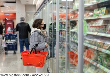 Caucasian Woman In Black Face Mask With Red Shopping Basket