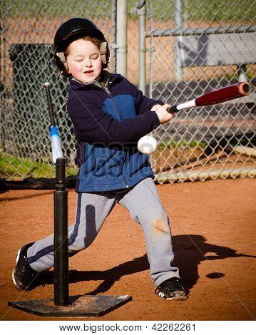 Boy batting at t-ball practice