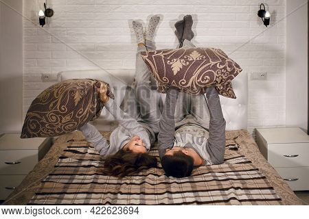 A Young Heterosexual Couple Is Lying On The Bed With Their Feet Against The Wall And Pillow Fights.