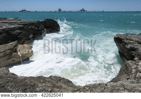 The View Of Grand Bahama Island Waves And Industrial Wet Dock Installation In A Background.