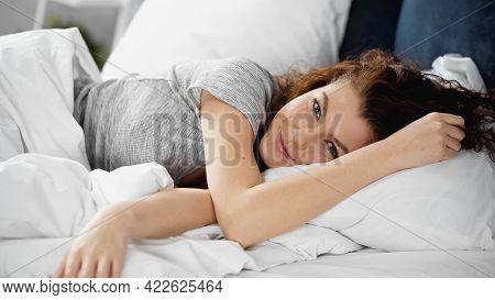 Smiling And Awake Young Woman Lying In Bed.