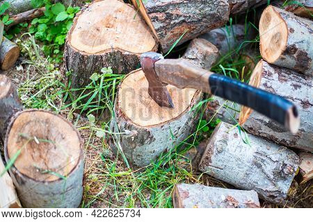 An Ax For Chopping Wood Is Stuck In A Log. Procurement Of Fuel For Heating The House In Winter.