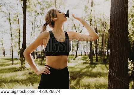 woman runner using earphones, takes a break and drinking water