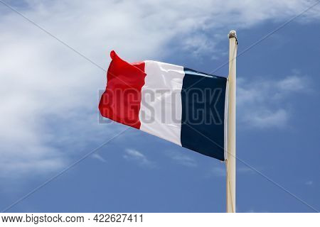 French flag with blue sky and white clouds