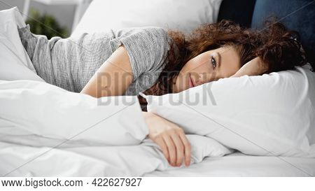 Awake Young Woman Looking At Camera While Lying In Bed.