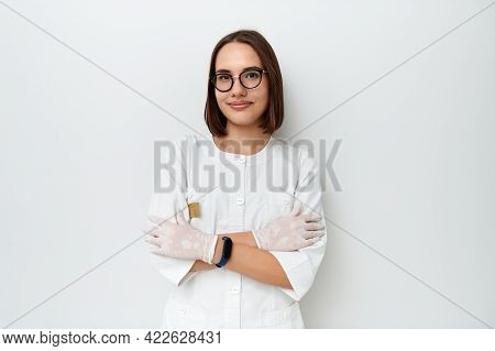 Charming Healthcare Worker In White Medical Uniform Poses In Front Of Camera With Crossed Arms On Ch
