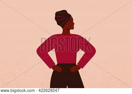 Strong Black Girl In Head Scarf With Hands On Her Hips Looks Forward. Confident Businesswoman Or Ent