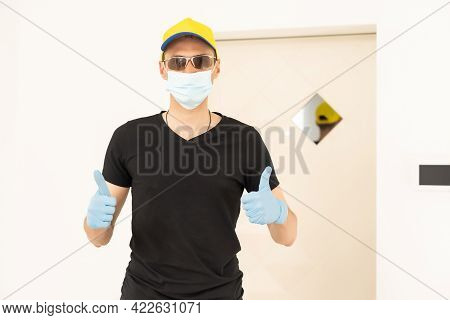 Confident Man Surgeon In Medical Mask On Face Wearing Protective Sterile Glove On Hand. Professional