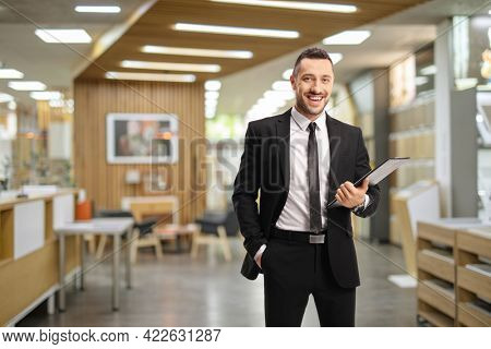 Salesman holding a clipboard inside a shop with wooden interior