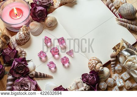 Transparent Pink Rpg Gaming Dice On An Open Sketchbook Framed By Seashells, Dried Pink Roses, And Wh