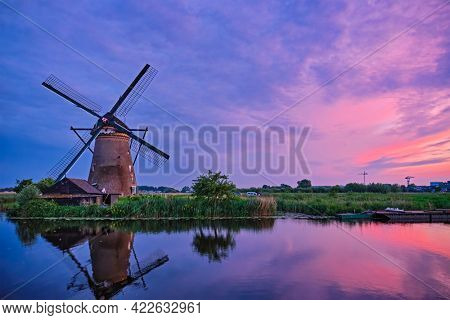 Netherlands rural lanscape with windmills at famous tourist site Kinderdijk in Holland in dusk with dramatic sky