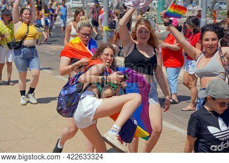 Gay And Lesbians Walking In The Gay Pride Parade. Parade Of Tolerance. Rainbow Flags At Gay Pride Pa