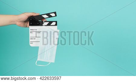 Fack Mask On Clapperboard And Hand Is Holding Clapper Board Or Movie Slate.it Is Used In Film Produc