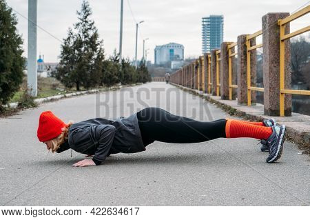 Fit Sporty Middle Aged Blonde 40s Woman In Red Cap Standing In Plank, Doing Workout, Stretching, Enj