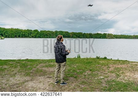 Man Playing With Drone For Exam. Silhouette Against Fresh Spring Landscape.male Operating The Drone