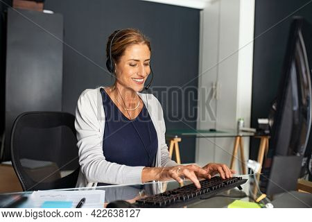 Happy smiling mature woman with headphone working from home. Beautiful businesswoman working as operator of call center or support service, smart working and telecommuting concept.