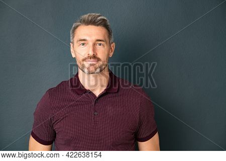 Portrait of middle aged man in casual clothing standing isolated on grey background. Successful mature man standing against gray wall and looking at camera. Confident reliable guy with copy space.