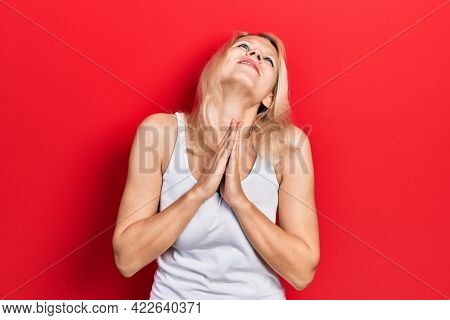 Beautiful caucasian blonde woman wearing casual white t shirt begging and praying with hands together with hope expression on face very emotional and worried. begging.