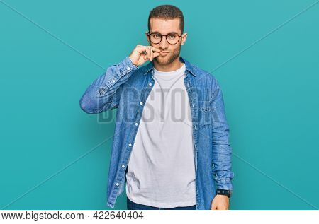 Young caucasian man wearing casual clothes mouth and lips shut as zip with fingers. secret and silent, taboo talking