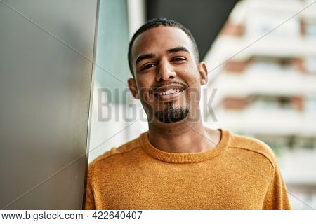 Young african american man smiling happy standing at the city.