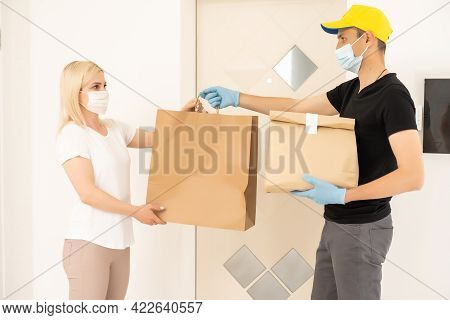 The Shipper Wears A Mask And Gloves, Delivery Food To The Home Of The Online Buyer. Stay At Home Red
