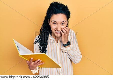 Young hispanic woman with curly hair holding book laughing and embarrassed giggle covering mouth with hands, gossip and scandal concept