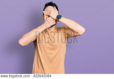 Hispanic man with beard wearing casual t shirt covering eyes and mouth with hands, surprised and shocked. hiding emotion
