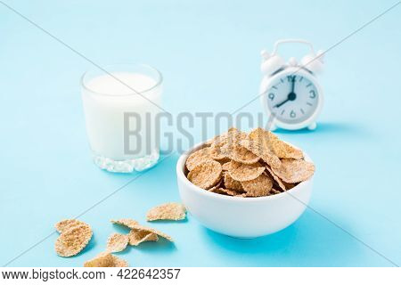 A Bowl Of Cereal, A Glass Of Milk And An Alarm Clock On A Blue Background. Scheduled Breakfast