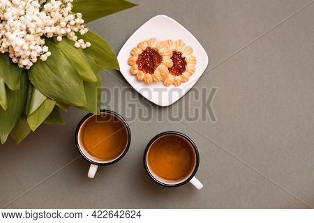 Two Mugs With Tea, Cookies On A Plate And Bouquets Of Lilies Of The Valley On A Green Background. Pa