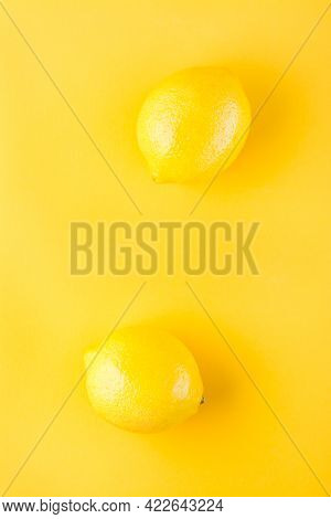 Two Ripe Whole Lemons On A Yellow Background. Detox Fruit Diet, Body Detoxification. Top And Vertica