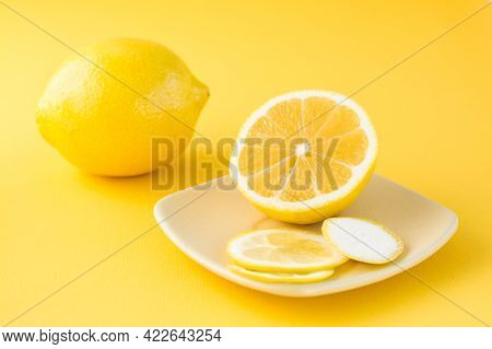 Sliced Lemon On A Saucer And A Whole Lemon Next To It On A Yellow Background. Detox Fruit Diet, Body