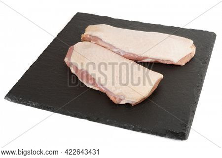 Two fatty duck fillets on black slate plate, isolated on white background