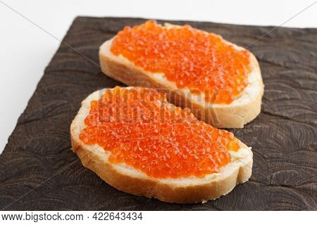 Two loaves of bread with red salmon roe on wooden board