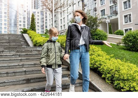 Portrait Of Young Adult Caucasian Mother Walking Downstairs Together With Little Daughter Kid In Cit