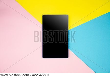 Mockup Black Blank Tablet Screen Display On Yellow, Blue, Pink Background. Flat Lay, Top View. Copy