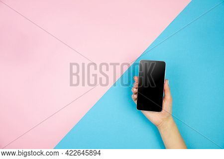 Young Woman Hand Holding Smartphone With Black Screen On Light Pink Blue Table Background. Copy Spac