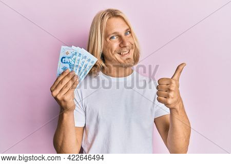 Caucasian young man with long hair holding 50 thai baht banknotes smiling happy and positive, thumb up doing excellent and approval sign