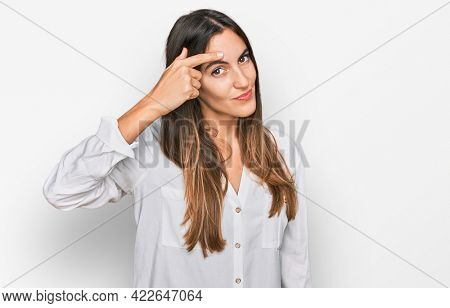 Young beautiful woman wearing casual clothes pointing unhappy to pimple on forehead, ugly infection of blackhead. acne and skin problem
