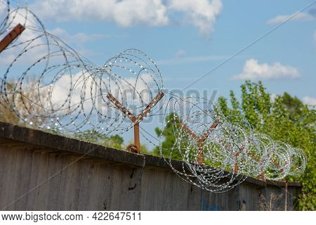 Close-up View Of Barb Wire Over Concrete Fence