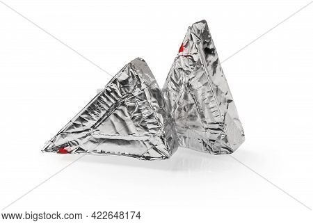 Two Triangular Pieces Of Foil Wrapped Processed Creame Cheese Isolated On A White Background. Tasty