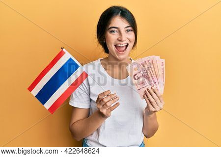 Young caucasian woman holding thailand flag and baht banknotes smiling and laughing hard out loud because funny crazy joke.