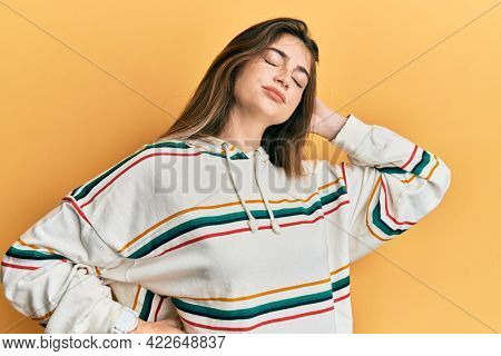 Young caucasian woman wearing casual clothes suffering of neck ache injury, touching neck with hand, muscular pain
